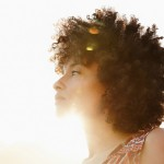 Low angle view of face of mixed race woman with lens flare